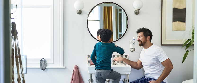 A father helping his child brush teeth
